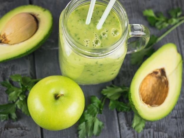 Vers gemaakte smoothies van avocado met kruiden en twee cocktailrietjes op een zwarte houten tafel. dieet vegetarisch eten.