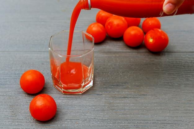 Vers gemaakte tomatensap in een houten bord van glazen kruik.