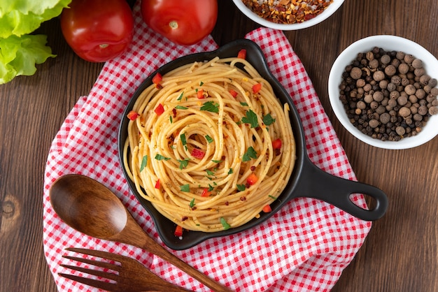 Vers gemaakte zelfgemaakte pasta met saus in keramiek op een houten achtergrond.