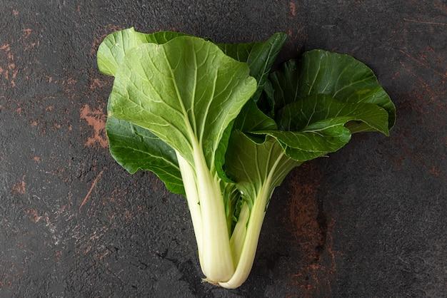 Vers geoogste biologische paksoi chinese kool verse salade op zwarte achtergrond