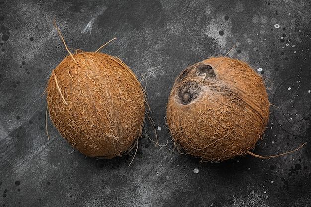 Vers geoogste kokosnoot set, op zwarte donkere stenen tafel achtergrond, bovenaanzicht plat lag