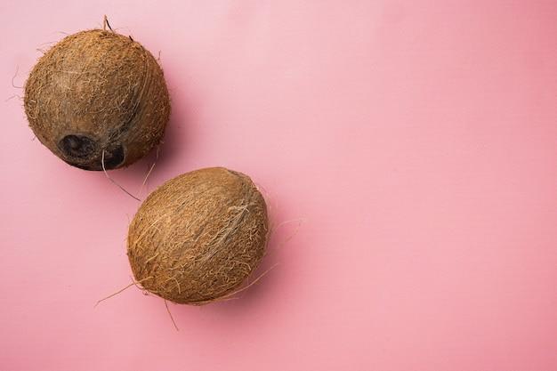 Vers geoogste kokosnootset, op roze getextureerde zomerachtergrond, bovenaanzicht plat, met kopieerruimte voor tekst