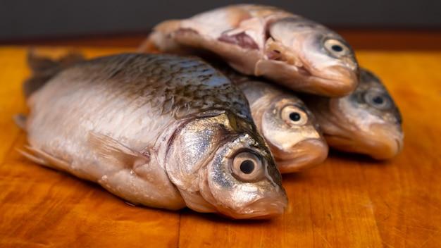 Vers gepelde vis, kroeskarper op de plank.
