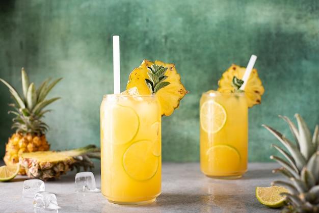 Vers geperst ananassap met partjes limoen en ijs in glazen potten
