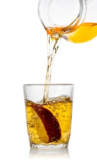 Vers geperst appelsap giet in glas met een appelschijfje
