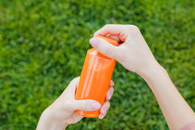 Vers geperst sinaasappelsap of wortelsap in een fles tegen een achtergrond van groen gras