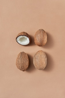 Vers geplukt fruit van drie rijpe hele kokosnoten en de ene helft op een lichtbruine achtergrond met zachte schaduwen, kopieerruimte. vegetarisch voedselconcept.