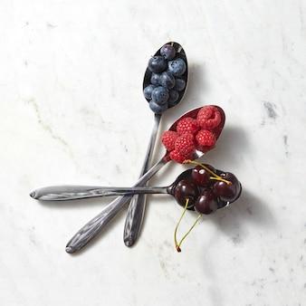 Vers geplukte framboos, kers, bosbes in lepels op een grijze achtergrond met plaats onder tekst. lepels kruisen elkaar op tafel