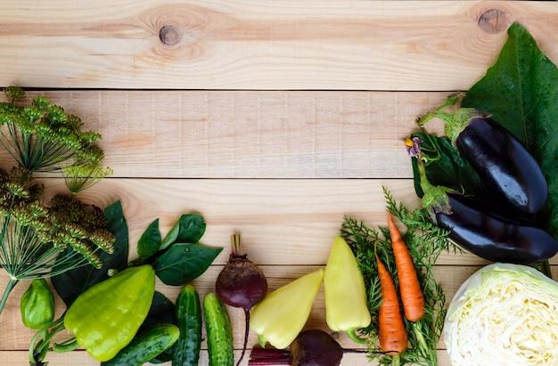 Vers geplukte groenten en kruiden op een hout. bovenaanzicht