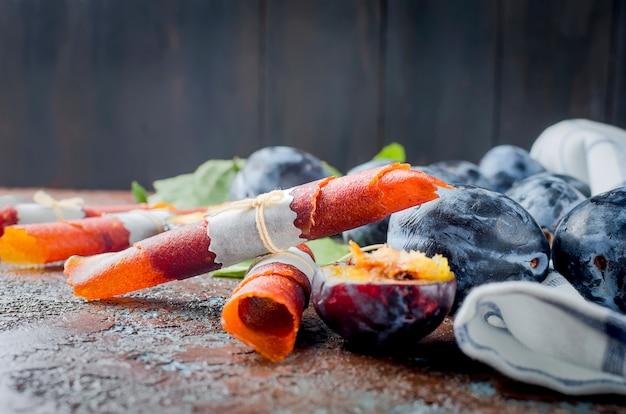 Vers geplukte pruimen op tafel en pruimenpastille op donkere ondergrond