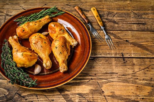 Vers gerookte kip drumsticks op een rustieke plaat met kruiden op houten tafel. bovenaanzicht.