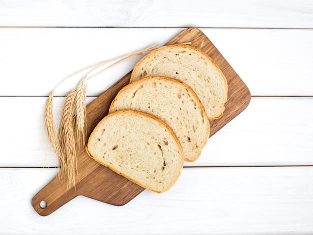Vers gesneden brood en tarwe op houten snijplank op witte houten tafel, bovenaanzicht