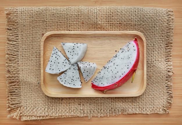 Vers gesneden draakfruit op houten dienblad en zak tegen houten raadsachtergrond.
