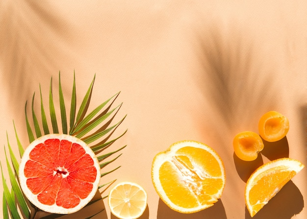 Vers gesneden fruit plat lag op beige achtergrond bij zonlicht