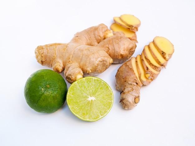 Vers gesneden gemberwortel en groene citroen die op witte oppervlakte wordt geïsoleerd.