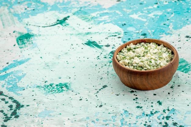 Vers gesneden koolsalade met greens binnen bruine kom op helderblauw bureau