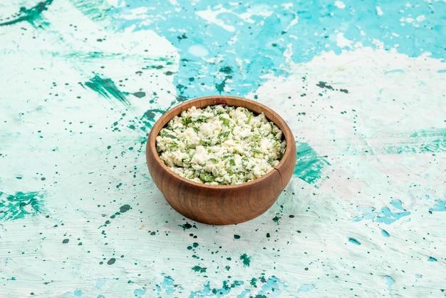 Vers gesneden koolsalade met greens binnen bruine kom op helderblauw