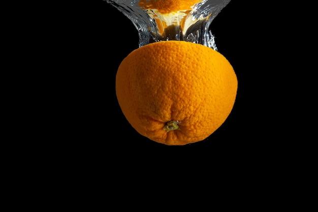 Vers gesneden oranje fruit in waterplons die op zwart wordt geïsoleerd.