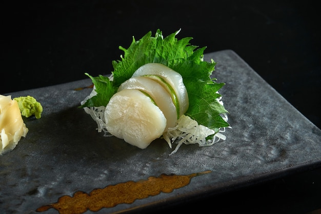 Vers gesneden sashimi van sint-jakobsschelp met daikon radijs geserveerd op een zwarte plaat op een zwarte tafel. japans eten