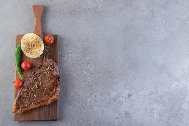 Vers gesneden vlees met verse groenten op een stenen achtergrond.