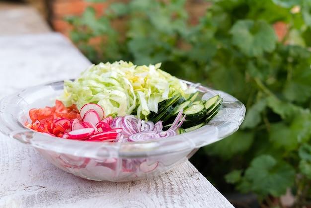 Vers gesneden zomersalade. veel heerlijke groenten in een glazen slakom.