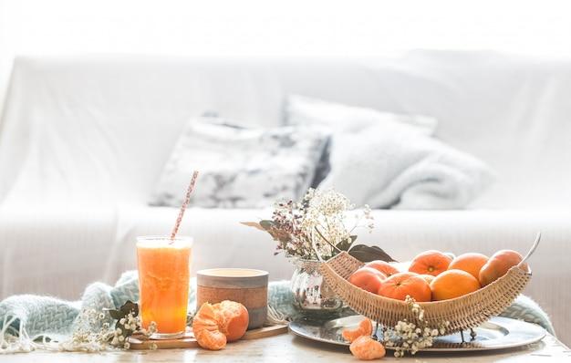 Vers geteeld biologisch vers sinaasappelsap in het interieur van het huis, met een turquoise deken en een fruitmand