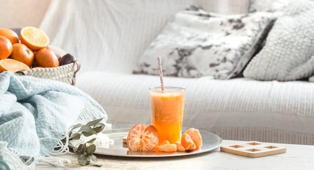 Vers geteelde biologische verse jus d'orange in het huis, met een turquoise deken en een fruitmand
