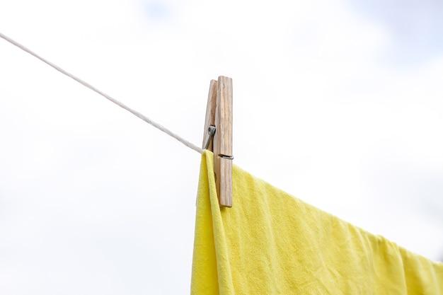 Vers gewassen beddengoed dat buiten aan het touw hangt. kleren drogen in landelijke tuin.