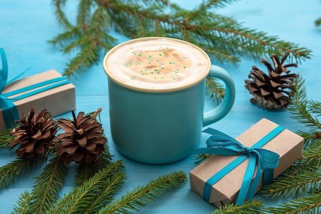 Vers gezette koffie met een luchtig schuim op een lichtblauwe houten tafel. met cadeautjes en dennennaalden.