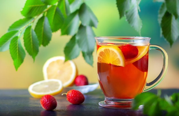 Vers gezette thee met citroen en aardbeien in een grote glazen beker