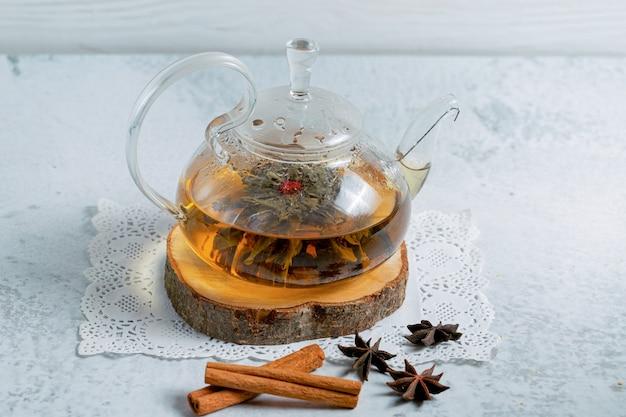 Vers gezette thee. theepot op een houten bord over grijze ondergrond.