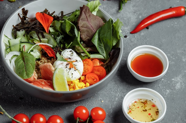 Vers gezond licht ontbijt, zakenlunch. ontbijt met gepocheerd ei, boekweit, rode vis, verse salade, komkommers, business lunch concept