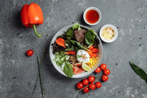 Vers gezond licht ontbijt, zakenlunch. ontbijt met gepocheerd ei, boekweit, rode vis, verse salade, komkommers en kerstomaatjes, zakenlunch concept.