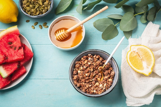 Vers gezond ontbijt: muesli, honing, watermeloen, citroen.