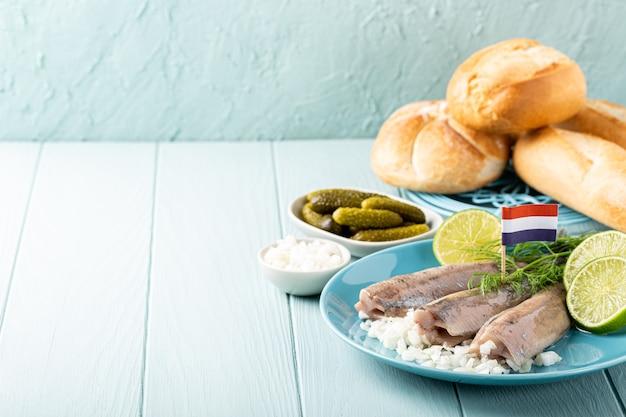 Vers gezouten haringvis, traditionele nederlandse delicatesse genaamd hollandse nieuwe op turkoois bord en houten oppervlak. europees voedselconcept met exemplaarruimte