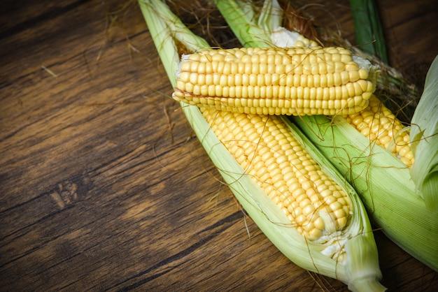 Vers graan op maïskolven en suikermaïsoren op rustieke houten lijst