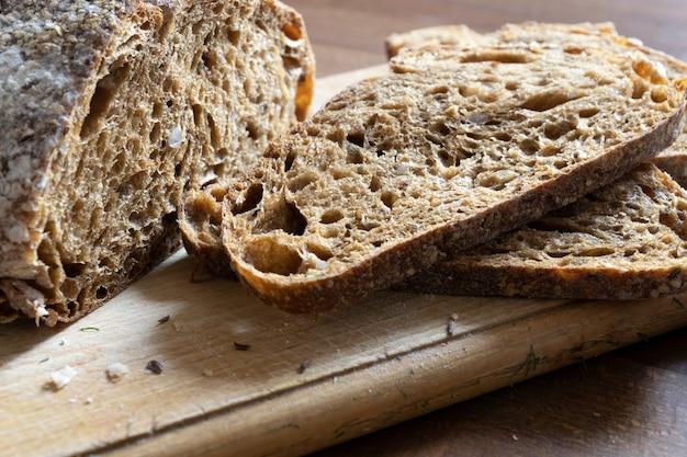 Vers graanbrood in plakjes gesneden op keukenbord, bovenaanzicht