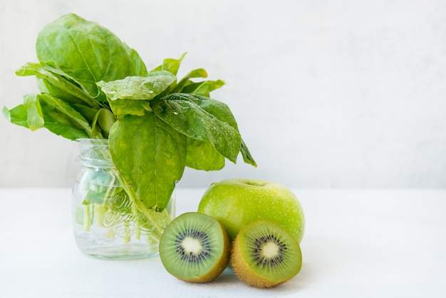 Vers groen fruit op een witte achtergrond, appel, kiwi en spinazie.