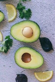 Vers groen geheel, gehalveerd en gesneden avocado en citroen, koriander en basilicum geïsoleerd op een stenen achtergrond