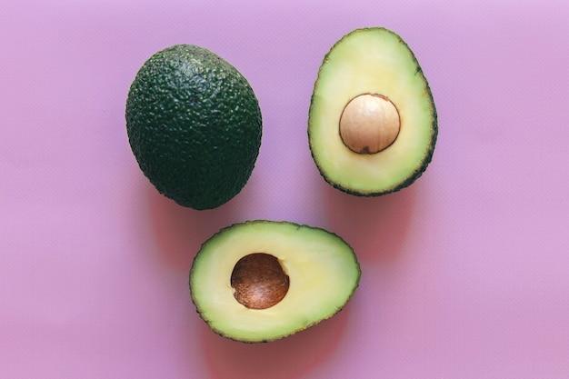 Vers groen in tweeën gesneden en hele avocado geïsoleerd op een roze achtergrond, bovenaanzicht, close-up, ruimte voor tekst.