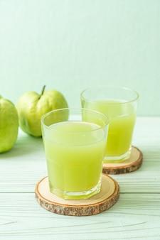 Vers guavesap glas met vers guave fruit op houten tafel