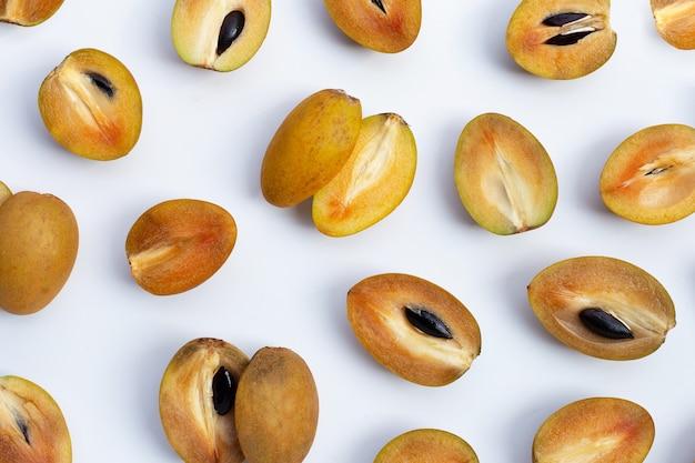 Vers half sapodillafruit dat op witte achtergrond wordt geïsoleerd. bovenaanzicht