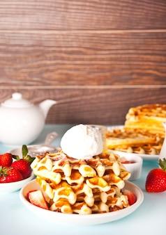 Vers huisgebakken wafels met aardbeien, honing en ijs