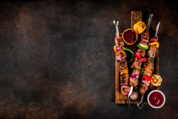Vers, huisgemaakt op de grill vuur vlees rundvlees shish kebab met groenten en kruiden, met barbecuesaus en ketchup, op een donkere achtergrond op een houten snijplank boven kopie ruimte