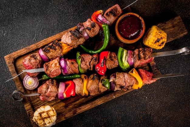 Vers, huisgemaakt op de grill vuur vlees rundvlees shish kebab met groenten en kruiden, met barbecuesaus en ketchup,