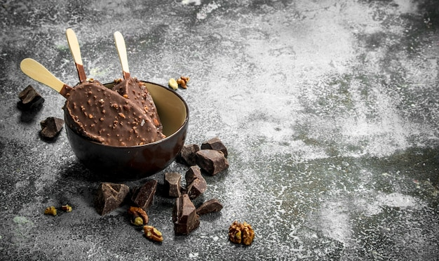 Vers ijs op een stokje in chocolade met noten. op een rustieke achtergrond.