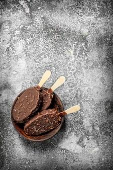 Vers ijs op een stokje in chocolade met noten op een rustieke achtergrond