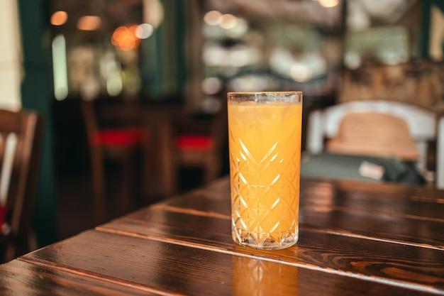 Vers ijs sinaasappelsap glas op houten tafel in een café of restaurant op heldere zonnige ochtenddag. dieet concept