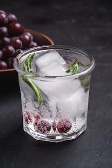Vers ijskoud koolzuurhoudend water in glas met rozemarijnblad dichtbij houten kom met druivenbessen