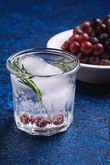 Vers ijskoud koolzuurhoudend water in glas met rozemarijnblad in de buurt van houten kom met druivenbessen, blauwe gestructureerde achtergrond, hoekmening macro